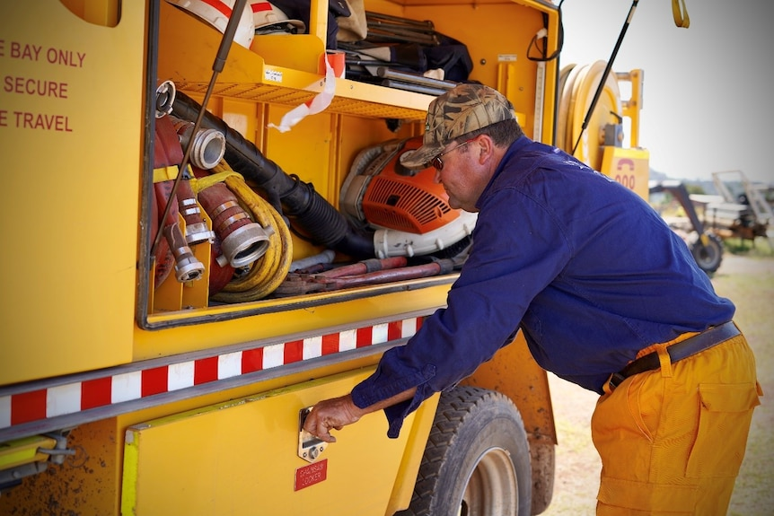 A photo of Anthony Sylvester wearing his fire brigade uniform and looking into a yellow fire truck.