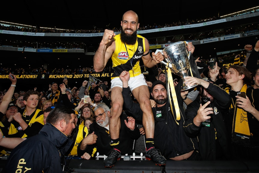 Bachar Houli stands on the MCG fence holding the AFL premiership cup. A crowd of Tigers fans celebrates behind him