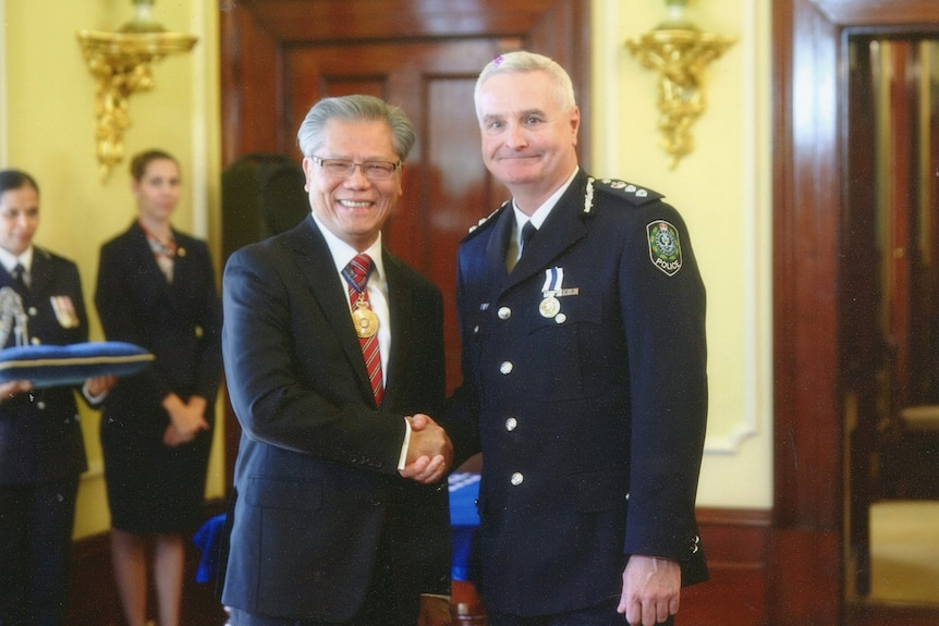 A man with grey hair and a suit shakes the hand of another, taller man with grey hair, wearing a formal police uniform