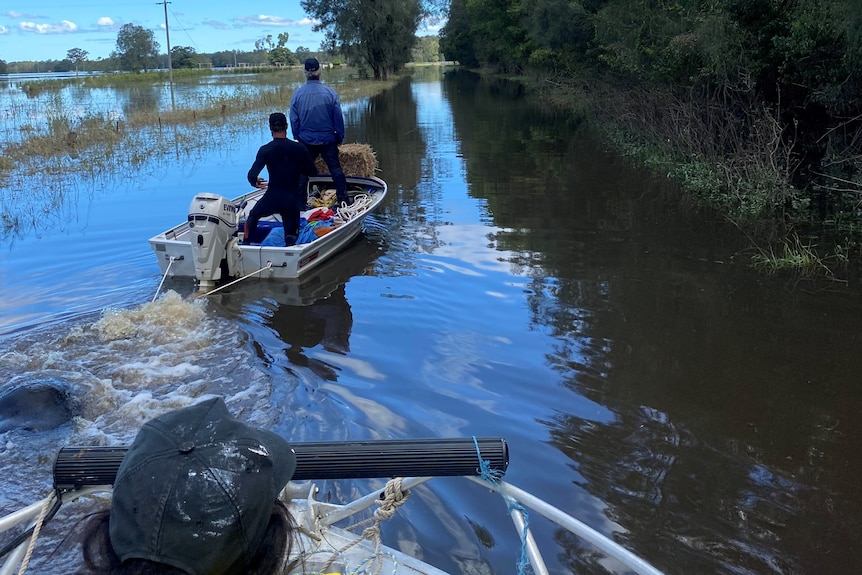 Two men in a boat navigating the floodwaters, while another follows.