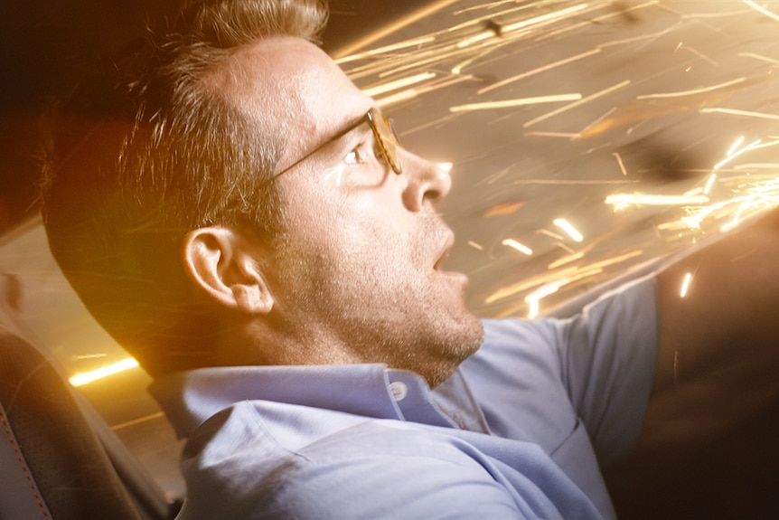 Ryan Reynolds driving recklessly in an action shot from the film Free Guy.