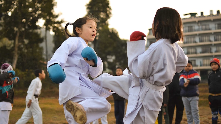 Two young children in martial arts uniforms spar outdoors, surrounded by other kids