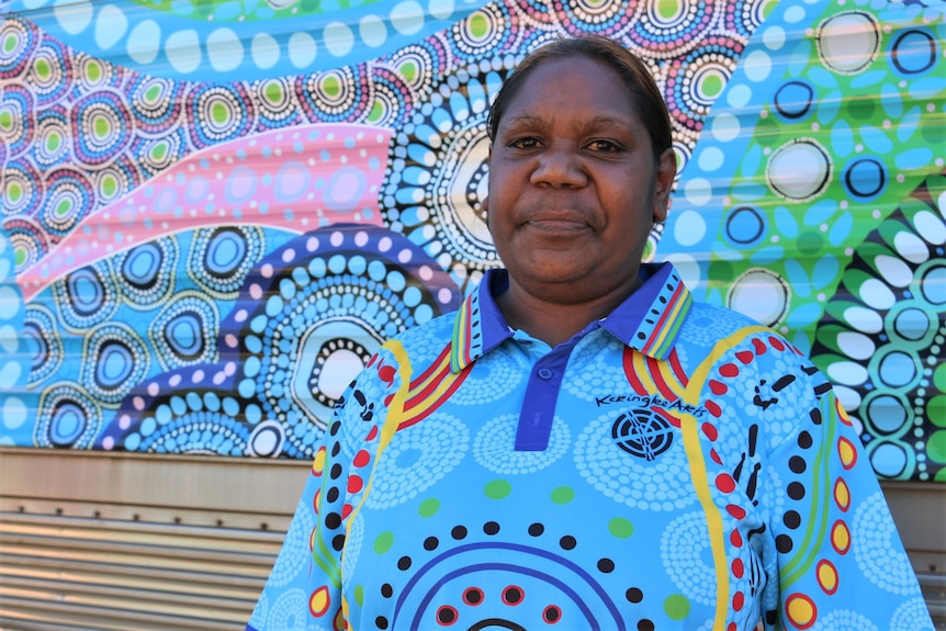 Indigenous woman wearing sky blue tshirt standing in front of train carriage with dot style artwork