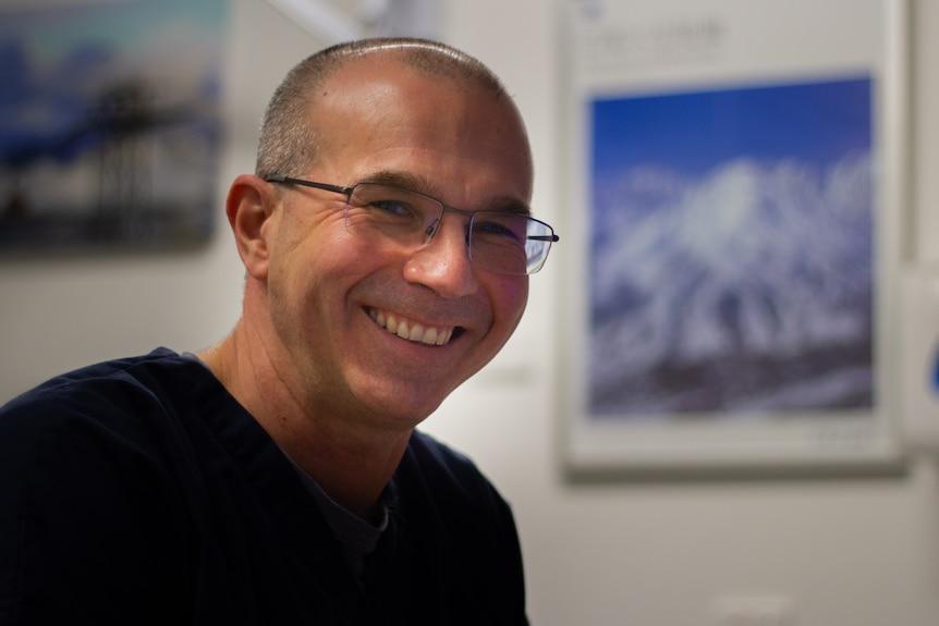 A headshot of a doctor smiling wearing blue scrubs in his office
