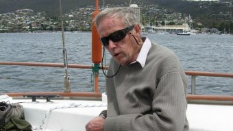 An older man sitting on a yacht.