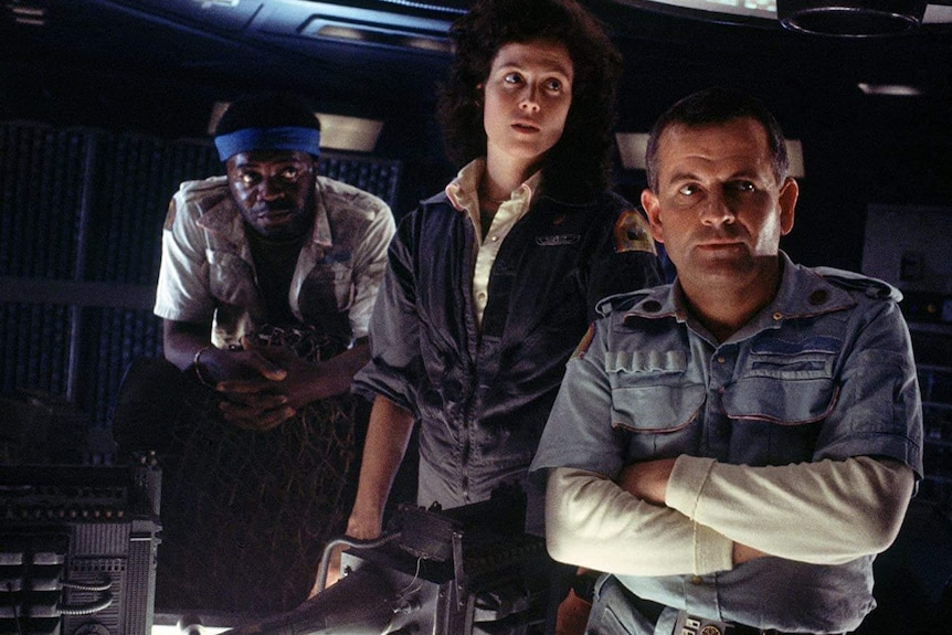 Yaphet Kotto, Sigourney Weaver and Ian Holm standing next to each other and looking off screen on the set of Alien