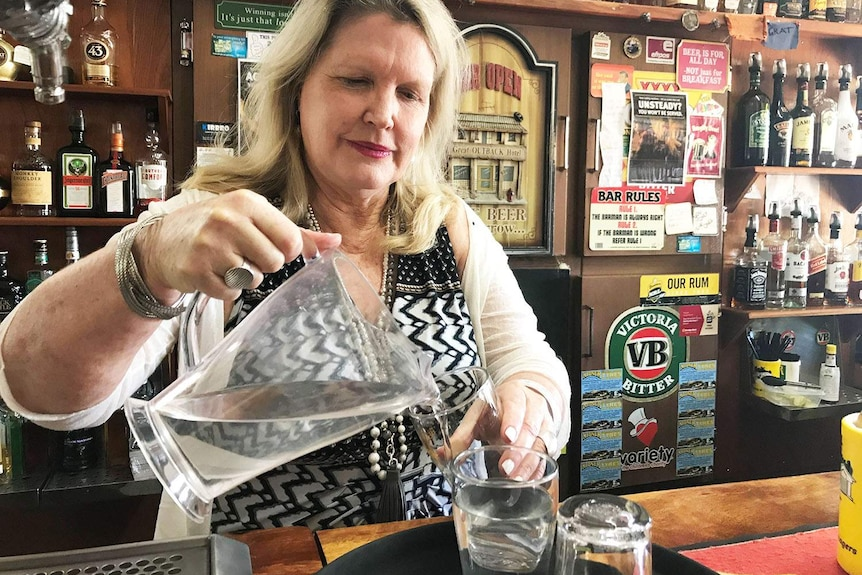 Lady behind a pub counter pours water from a jug into glasses.