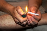 A man sits on the ground and lights a joint.
