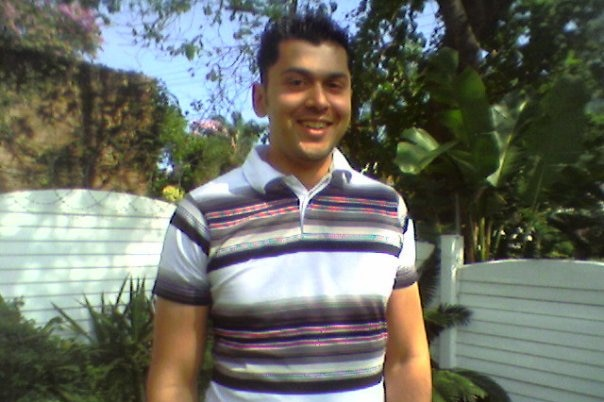 A young man in a striped polo shirt photographed in a garden.