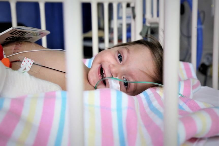 A baby in a hospital cot smiling through the bars.