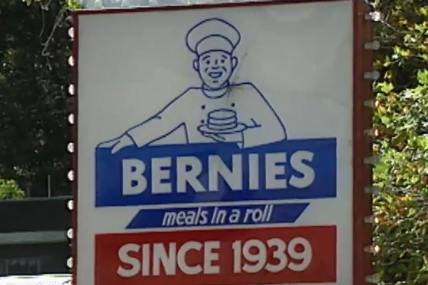 Blue white and red sign of man in chef outfit holding plate with burger on it