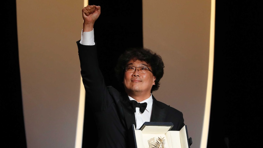 A Korean man holds a black leather box containing a metal palm as he throws is fist in the air onstage.
