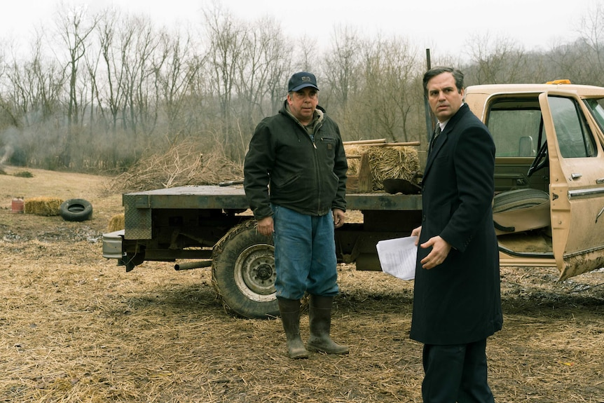 The actors Bill Camp as a farmer and Mark Ruffalo as a lawyer standing in a dry farm field with a pickup truck