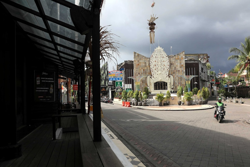 A motorist passes Ground Zero Memorial in Legian, where the streets are empty.