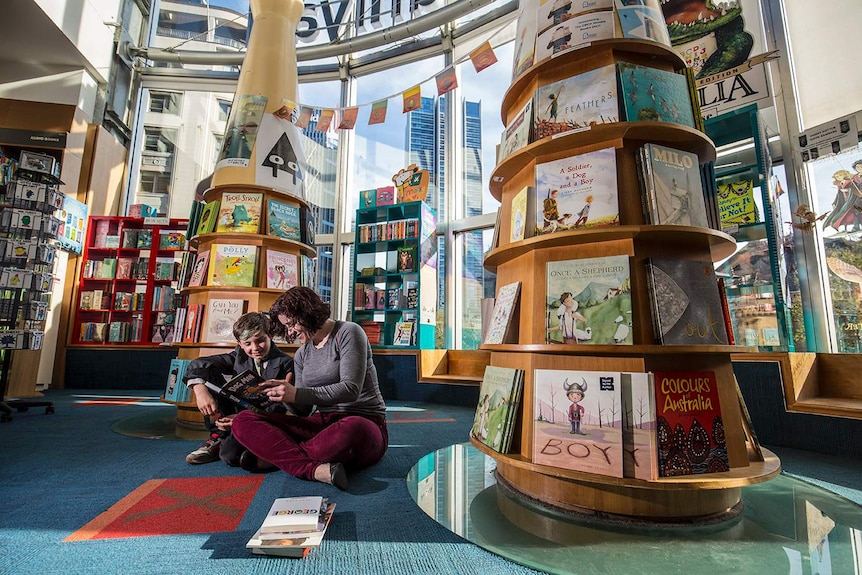 Colour photograph of mother and son reading a book in the children's books section in a Books Kinokuniya.