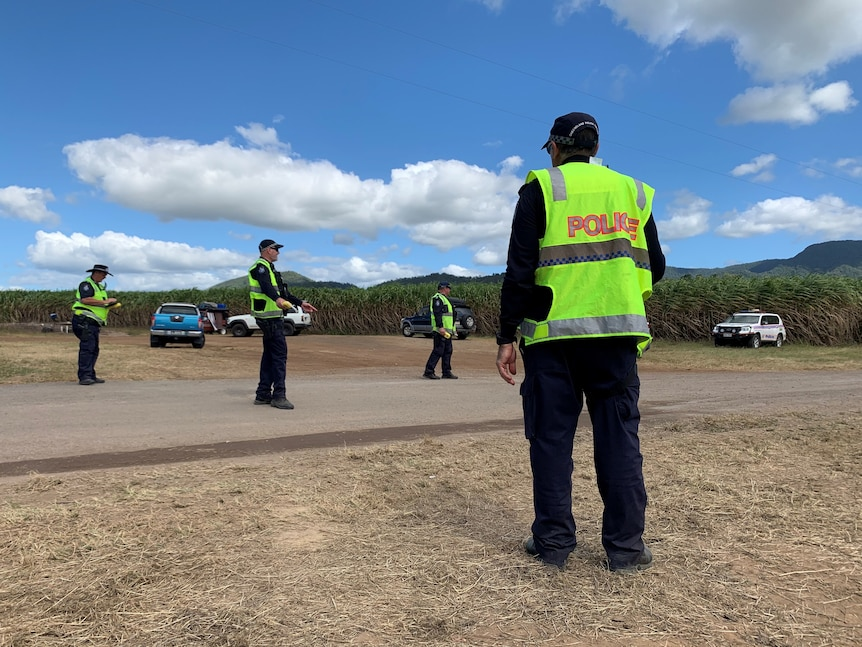 A number of police standing on a country road in hi-vis vests