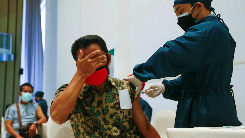 A man with his hand over his eyes gets a needle from a doctor.