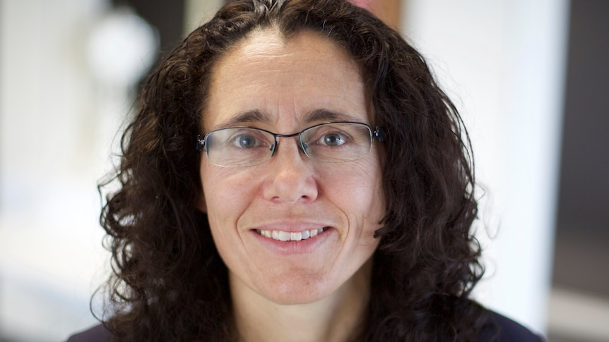 Closely cropped image of a woman with shoulder-length dark hair and glasses smiling.