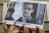 Supports hold up a picture of Edward Snowden