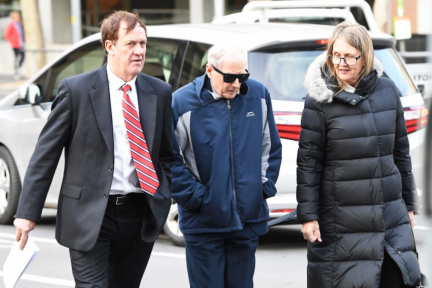 Former school principal and Marist Brother Gerard McNamara (centre) walks into court with a man and woman.