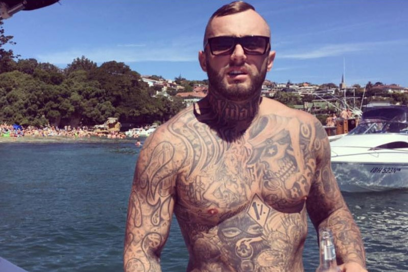 A heavily tattooed shirtless Michael Davey on a boat on the harbour.
