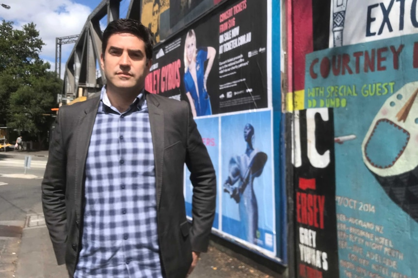 A man stands on the street, in front of a number of promotional posters for gigs.