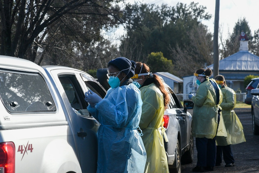 Two nurses in full PPE speak to the occupants of a white ute at a drive-through testing clinic.