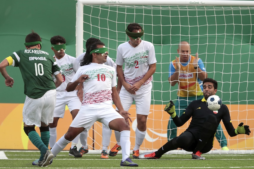 A Brazilian Paralympic footballer wearing blackout goggles takes a shot and the ball goes toward the sighted Iran goalkeeper.