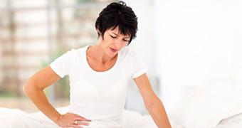 Woman holding her lower abdomen