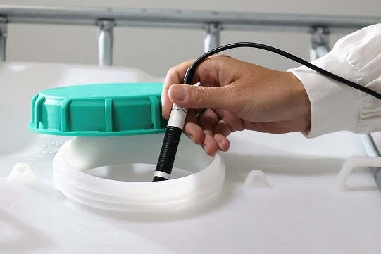 Hand in a white sleeve holds a black and white probe into a large plastic container with a green lid to the side.