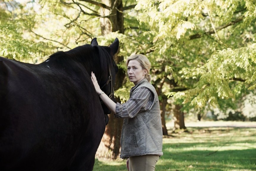 Carrie Coon pats a horse, looking concerned, in the film The Nest