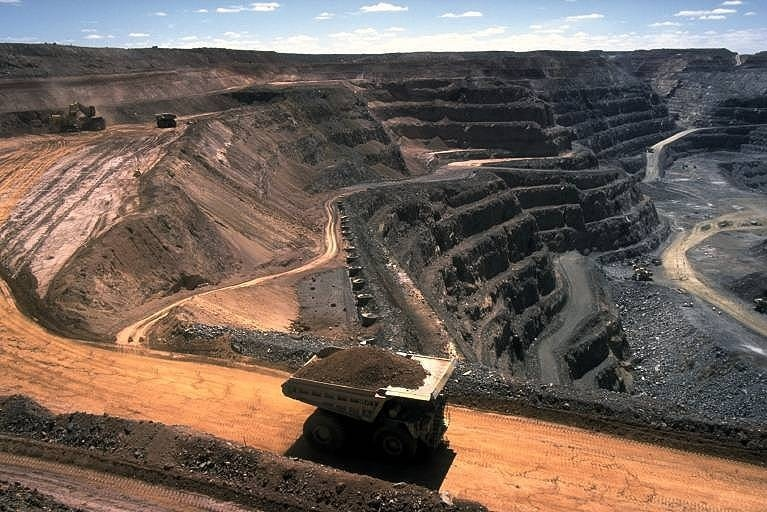 An aerial shot of an open cut coal mine, with a large truck transporting a pile of coal out up a dirt road.