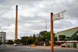 The sign for Ellen Street in the foreground with a large smoke stack from the lead smelter in the background
