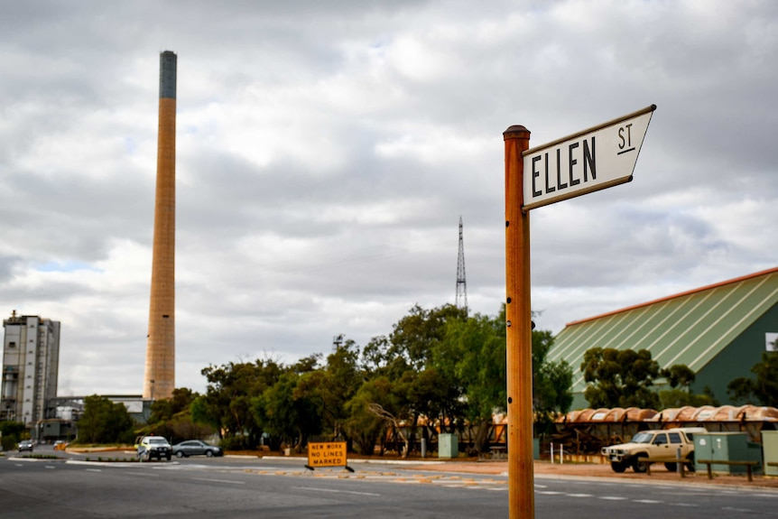 """A sign reading """"Ellen Street"""" in the foreground, with a large smoke stack from the lead smelter in the background."""