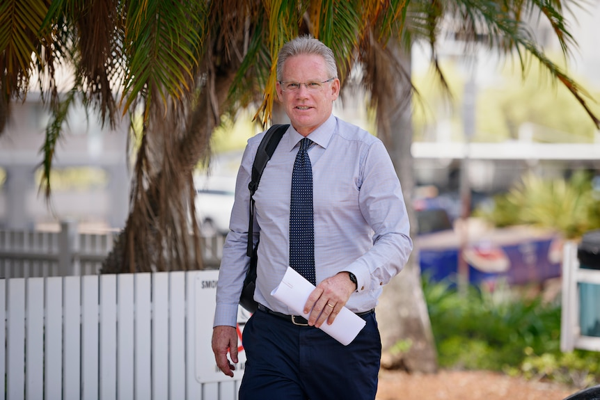 A middle-aged white man wearing a suit arrives at court