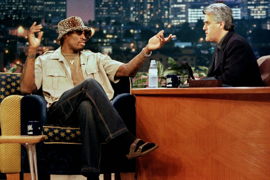 Basketballer Dennis Rodman wears a a leopard print hat while being interviewed by Jay Leno