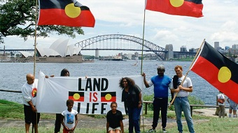 "People hold Indigenous flags and ""Land is Life"" sign in front of Sydney Harbour, Opera House and Sydney Harbour Bridge"