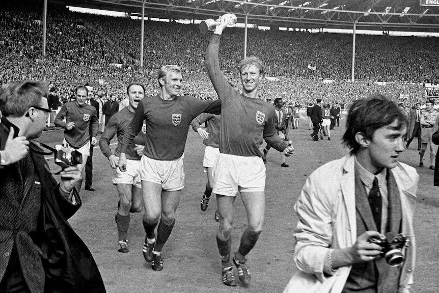 A black and white photo of Jack Charlton holding a trophy above his head at a packed Wembley