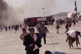 People run from an explosion across an airport tarmac.