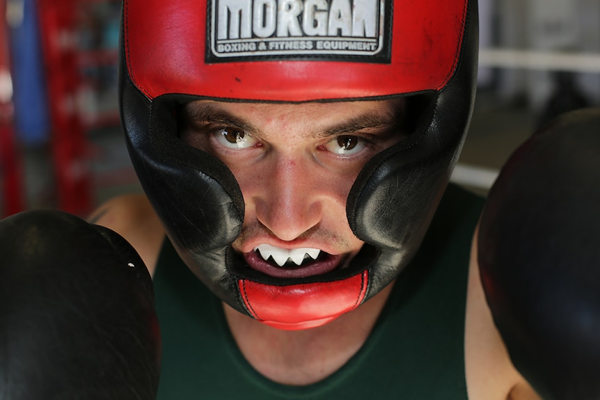 A boxer wears a red and black helmet as well as a white mouthguard and looks directly into the camera with gloves.