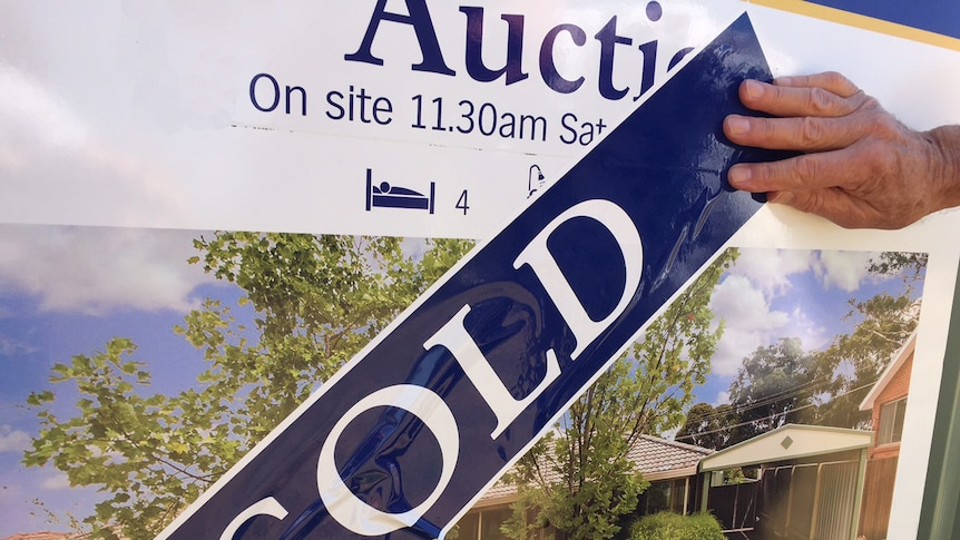 A hand smooths out a 'SOLD' banner over an auction billboard for a home.