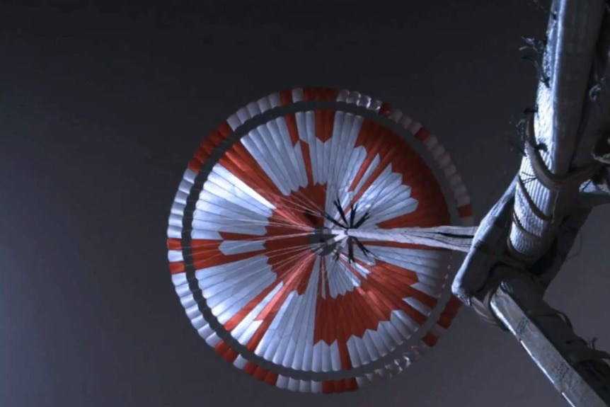 Photo looking up from NASA's Perseverance rover at the red and white parachute slowing it down upon landing on Mars