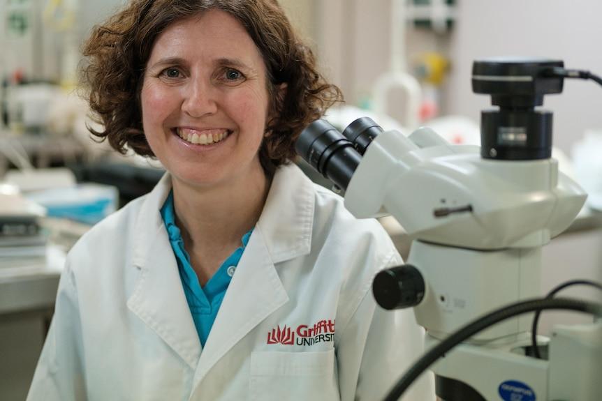 Una donna in camice bianco siede accanto a un microscopio