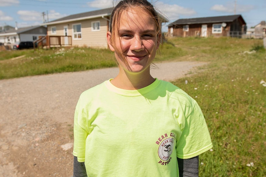 A young woman in a yellow t-shirt standing outside a house