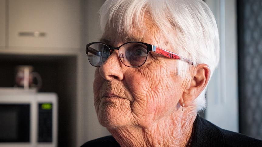 Yvonne Moss wearing glasses looks upwards.