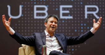 Travis Kalanick sits in front of the uber logo with his arms spread wide, open palmed drawing attention to the word UBER