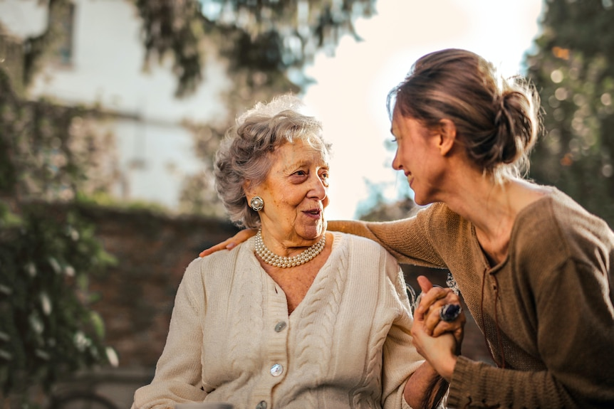 An elderly woman is talking with a younger woman. The young woman is turned away from the camera.