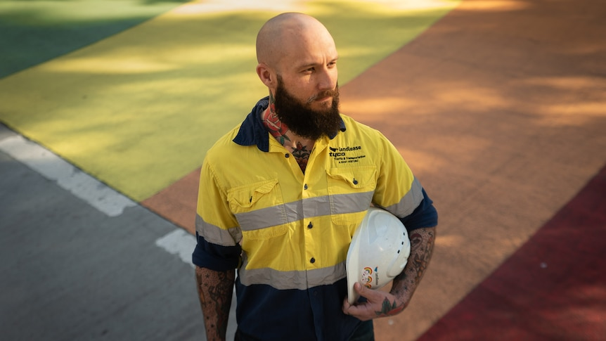 A bald man wearing hi-vis and carrying a white hard hat looks away to his left