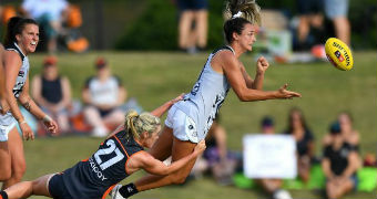 An AFLW player passes the ball in front of her as she is tackled from behind
