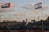 Women wearing face masks against the coronavirus walk past United Arab Emirates and Israeli flags at the Peace Bridge.
